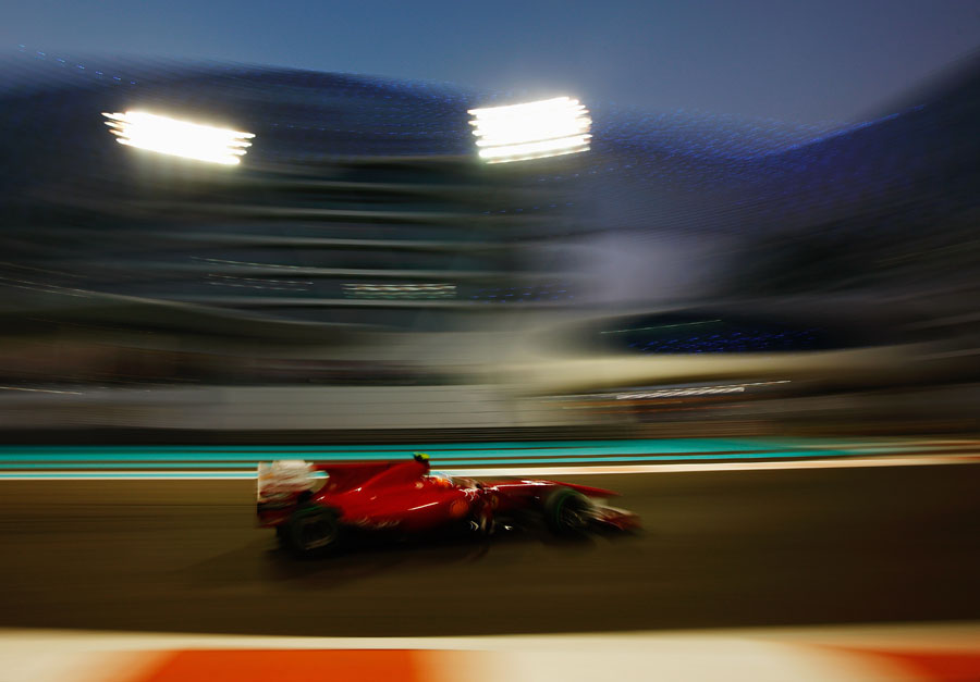 Fernando Alonso passes the Yas Hotel