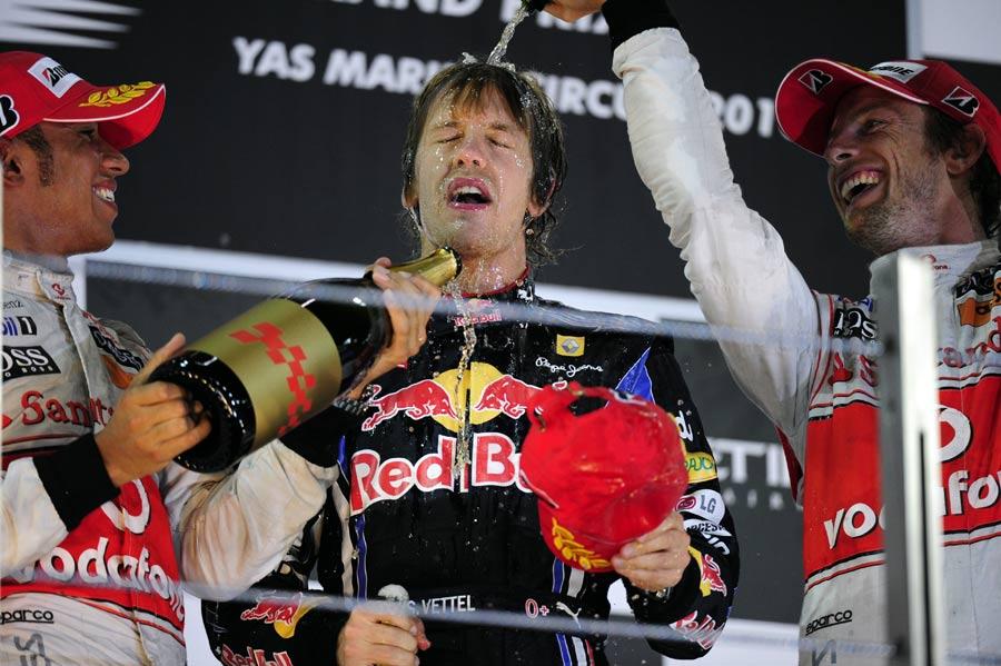 Lewis Hamilton and Jenson Button congratulate Sebastian Vettel on the podium