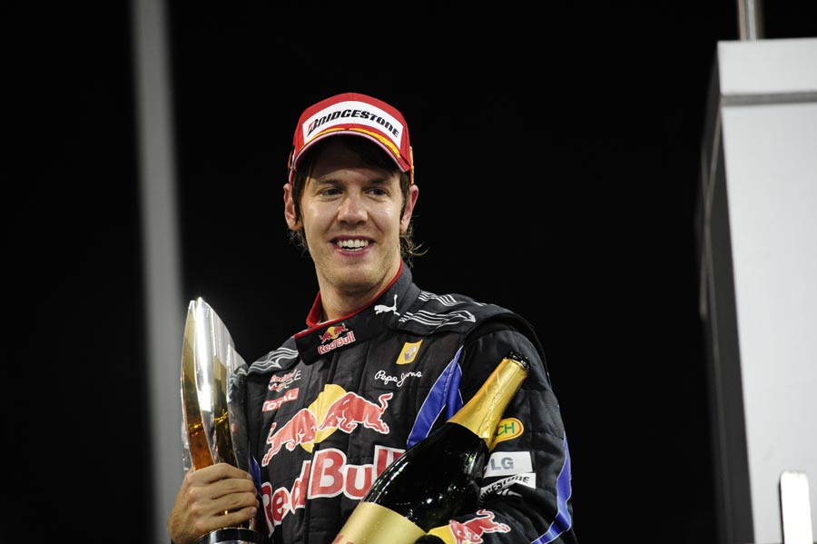 Sebastian Vettel with his trophy and champagne on the podium
