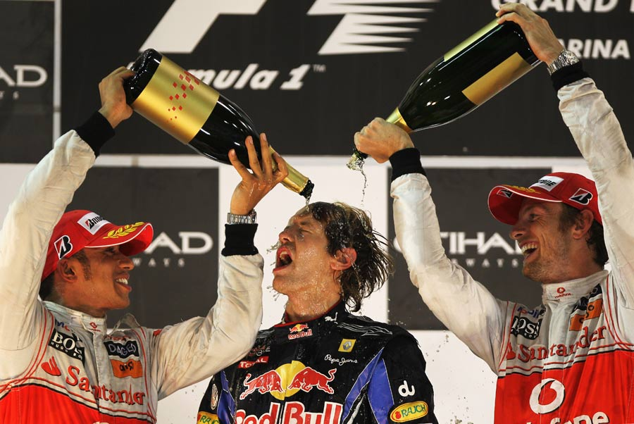 Lewis Hamilton and Jenson Button douse Sebastian Vettel with champagne