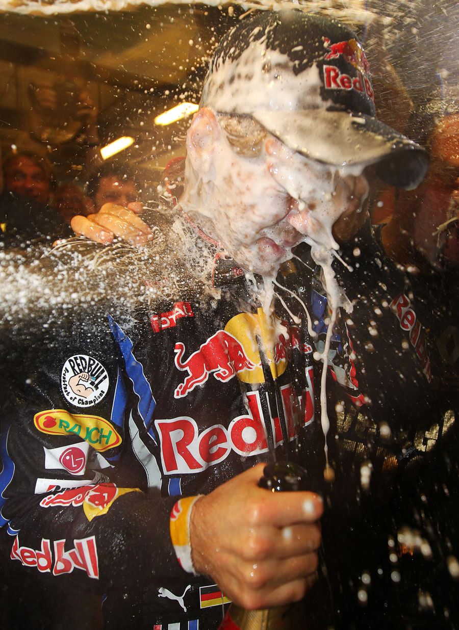 Sebastian Vettel gets doused with champagne in the Red Bull garage