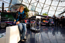 Sebastian Vettel takes a phone call during a press conference at Red Bull's headquarters