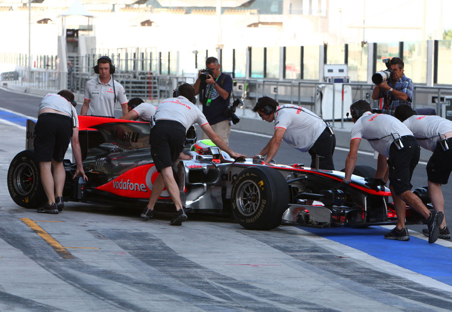 Oliver Turvey is wheeled back into the McLaren garage