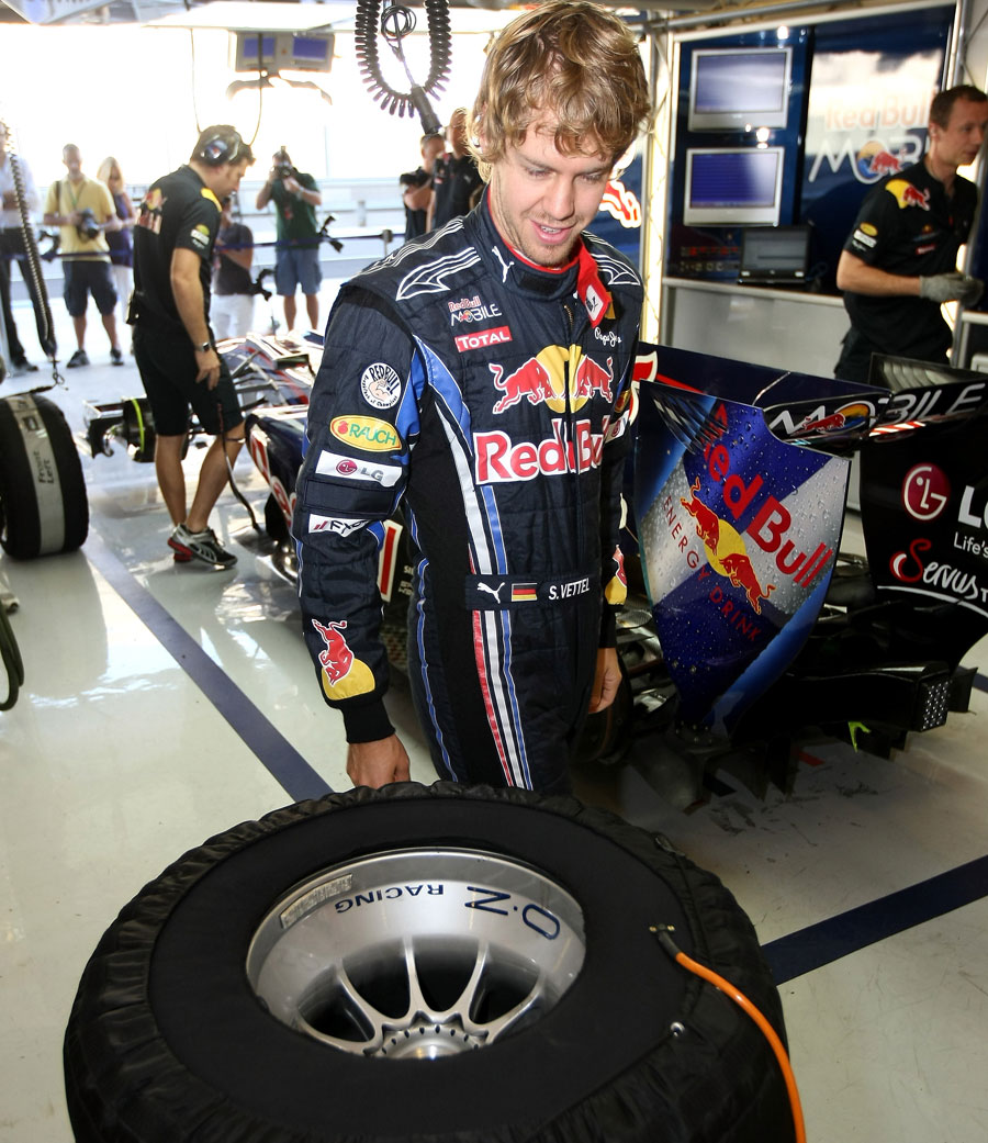Sebastian Vettel keeps an eye on his pre-heated tyres