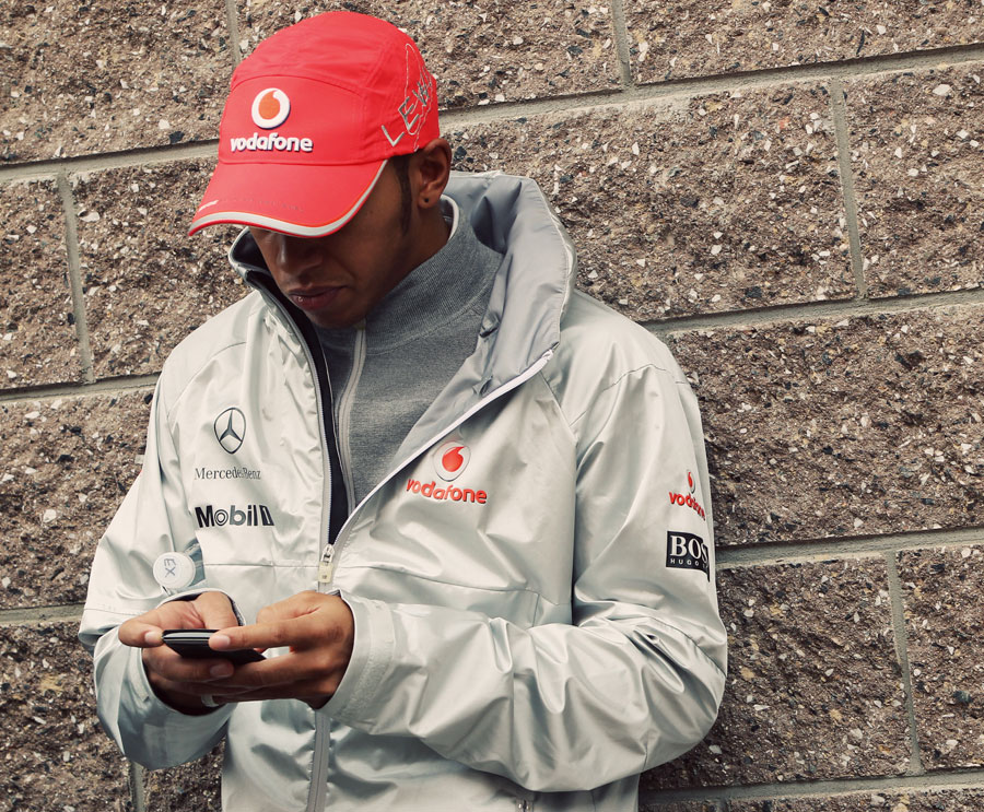 Lewis Hamilton uses his phone in the paddock