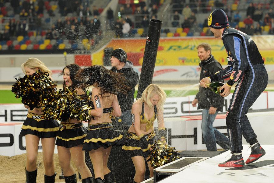 Sebastian Vettel sprays champagne over the dancing girls as he Michael Schumacher celebrate winning
