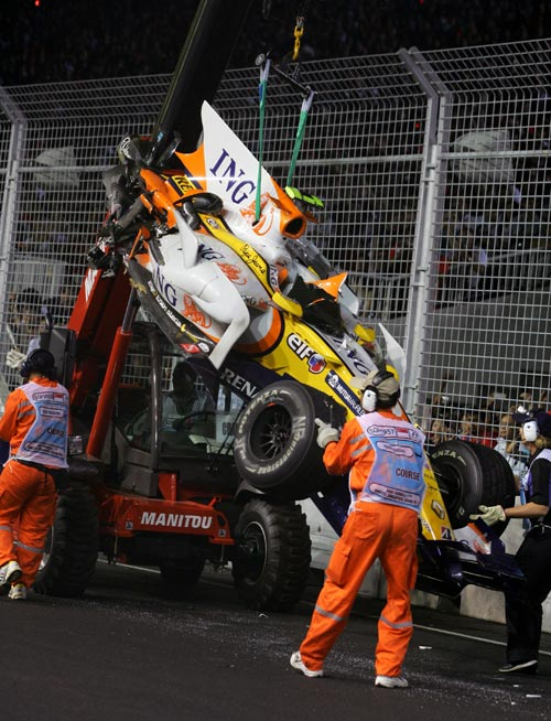 Nelson Piquet Jnr's car is retrieved after he crashed into the wall