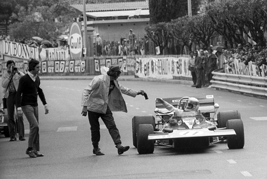Jackie Stewart receives a bottle of Coca-Cola from Tyrrell mechanic Richard Hill after winning the Monaco Grand Prix