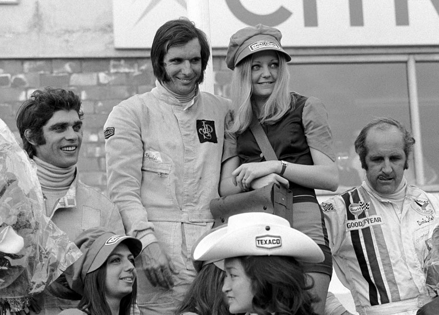 Emerson Fittipaldi celebrates on the podium with Francois Cevert and Denny Hulme