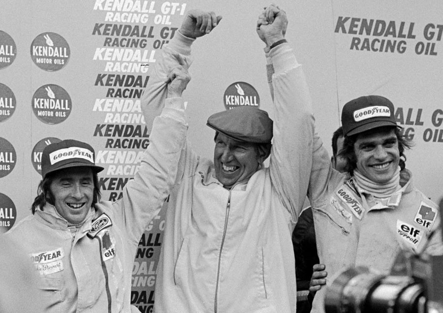Ken Tyrrell celebrates on the podium with drivers Jackie Stewart and Francois Cevert