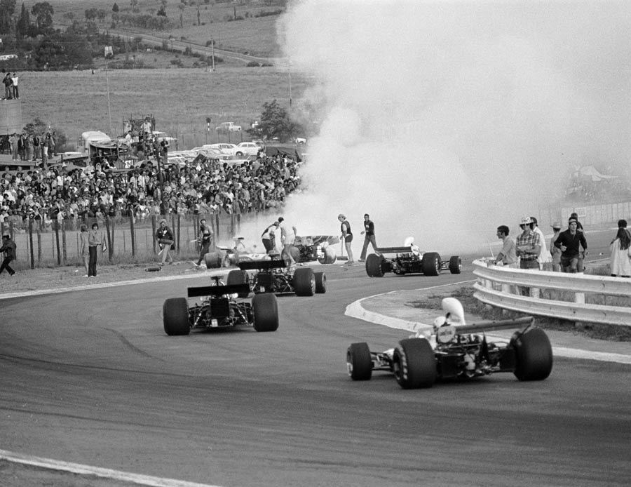 Cars stream past the fiery accident involving Mike Hailwood, Clay Regazzoni and Jacky Ickx