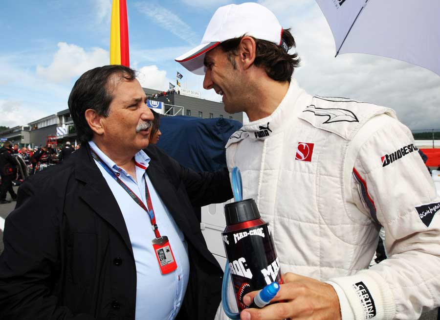 HRT owner Jose Ramon Carabante talks to Pedro de la Rosa on the grid