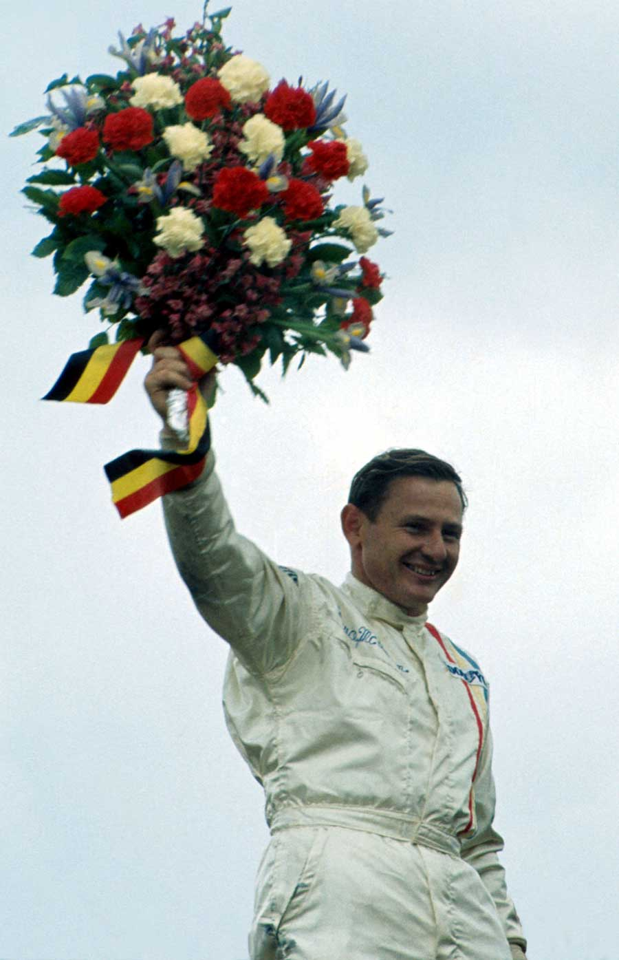 Bruce McLaren celebrates his and Team McLaren's first victory