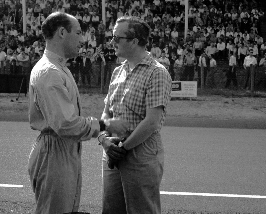 Stirling Moss chats to Lotus team boss Colin Chapman on the pit straight at Zandvoort