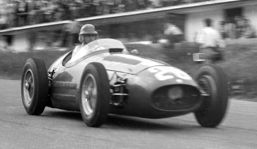 Juan Manuel Fangio at speed down the hill past the pits