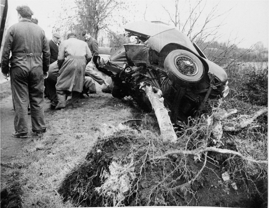 Police and mechanics probe the wreckage of the sports car in which Britain's Mike Hawthorn met his death
