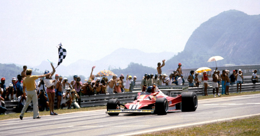 Carlos Reutemann  takes the chequered flag to secure his first race win