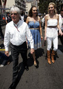 Bernie Ecclestone leads his daughters Tamara and Petra down the pit lane