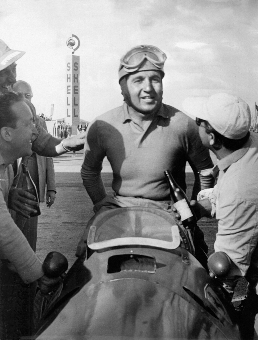 Alberto Ascari climbs from his Ferrari after wining the German Grand Prix and securing his first world title