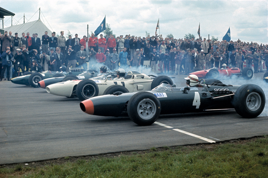Tyre smoke fills the air as the field moves off with Jackie Stewart nearest the camera, then Richie Ginther and Jim Clark, with John Surtees in the second row