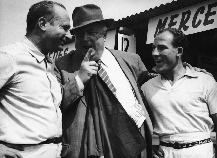Alfred Neubauer,  manager of the German Mercedes team, has a word with Juan Manuel Fangio and Stirling Moss