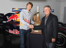 2010 champion Sebastian Vettel greets 1978 champion Mario Andretti at Red Bull's factory