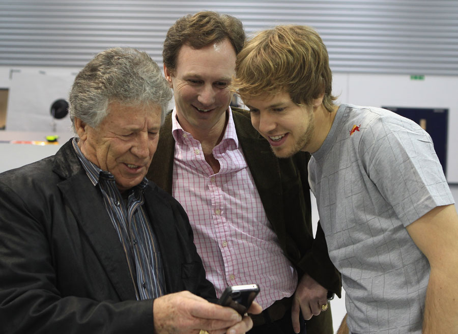 Mario Andretti shows off his phone to Christian Horner and Sebastian Vettel