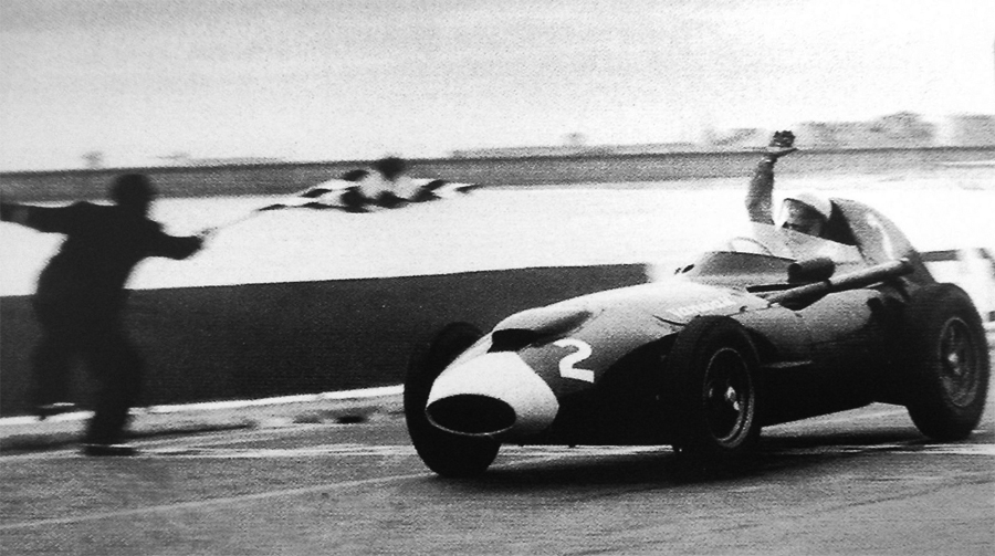 Stirling Moss takes the chequered flag to win the Portuguese Grand Prix