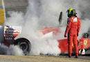 Felipe Massa stands to one side as his Ferrari smoulders