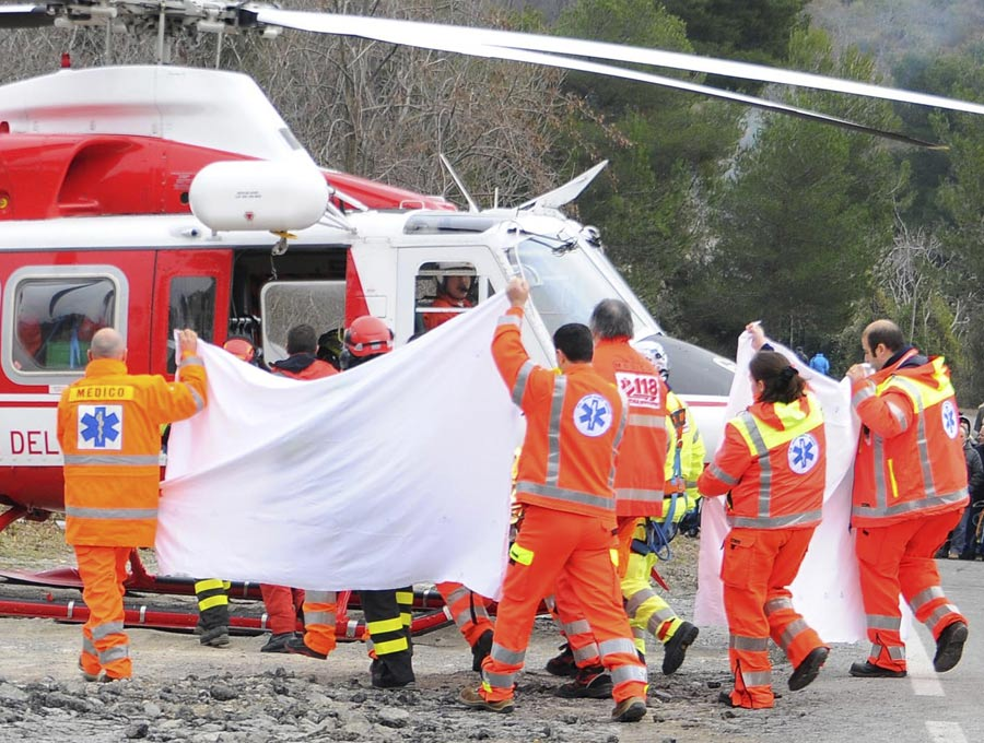 Italian paramedics use a sheet to cover the rescue of Robert Kubica