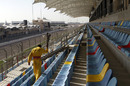 A worker cleans seats ahead of a grand prix that might not happen in Bahrain