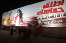 Protesters walk past a poster advertising the cancelled Bahrain Grand Prix, Manama