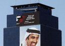 Workers high on an office tower remove a full-length advertisement for the cancelled Bahrain Grand Prix