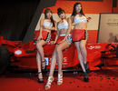Models pose with an F1 show car during the launch of the 2011 Korean Grand Prix in Seoul