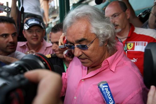 Flavio Briatore is mobbed by the media as he leaves a meeting at the Automobile Club de Monaco