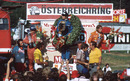 Carlos Reutemann stands on top of the podium with Denny Hulme to his right and James Hunt keeping the crowd entertained to his left