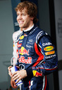 Sebastian Vettel smiles for the cameras after taking pole position