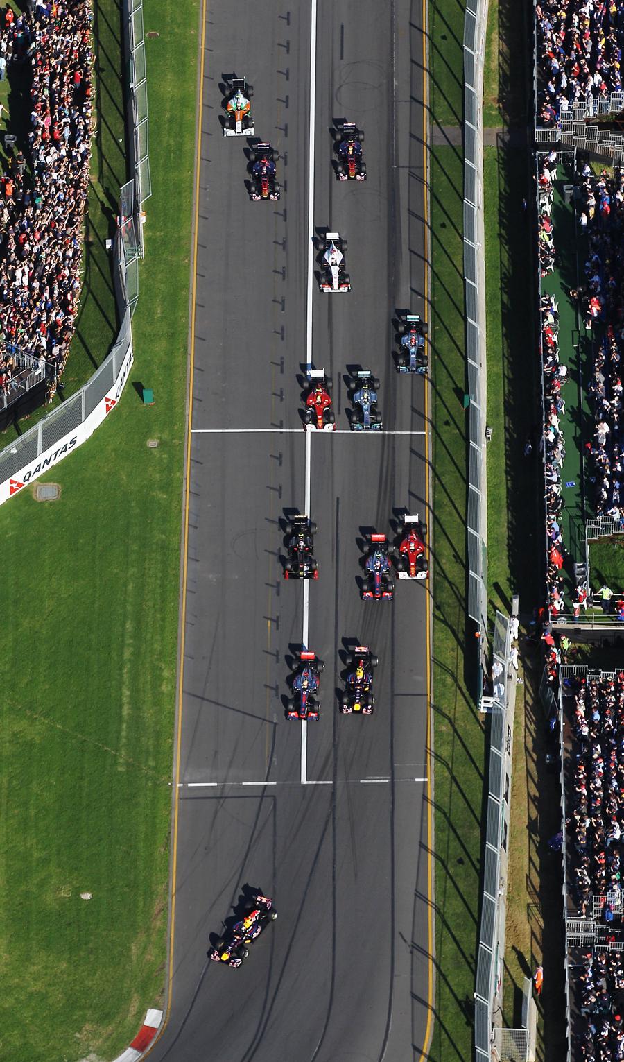 Sebastian Vettel leads the field as Fernando Alonso gets squeezed wide
