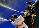 Second-place Lewis Hamilton and third-placed Vitaly Petrov spray the champagne
