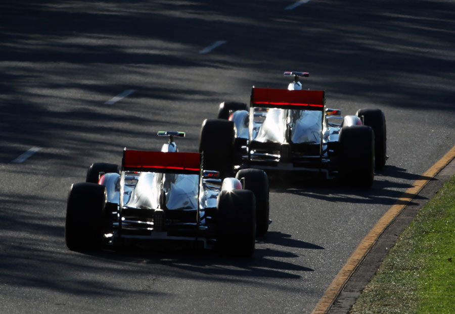 The McLarens of Jenson Button and Lewis Hamilton run nose-to-tail out of turn two