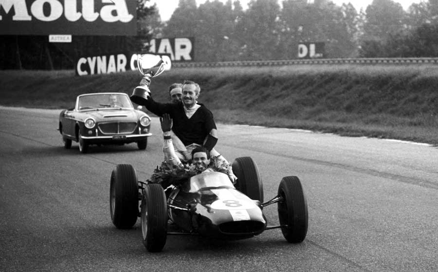 Jim Clark gives Colin Chapman a lift round the circuit with the winner's trophy