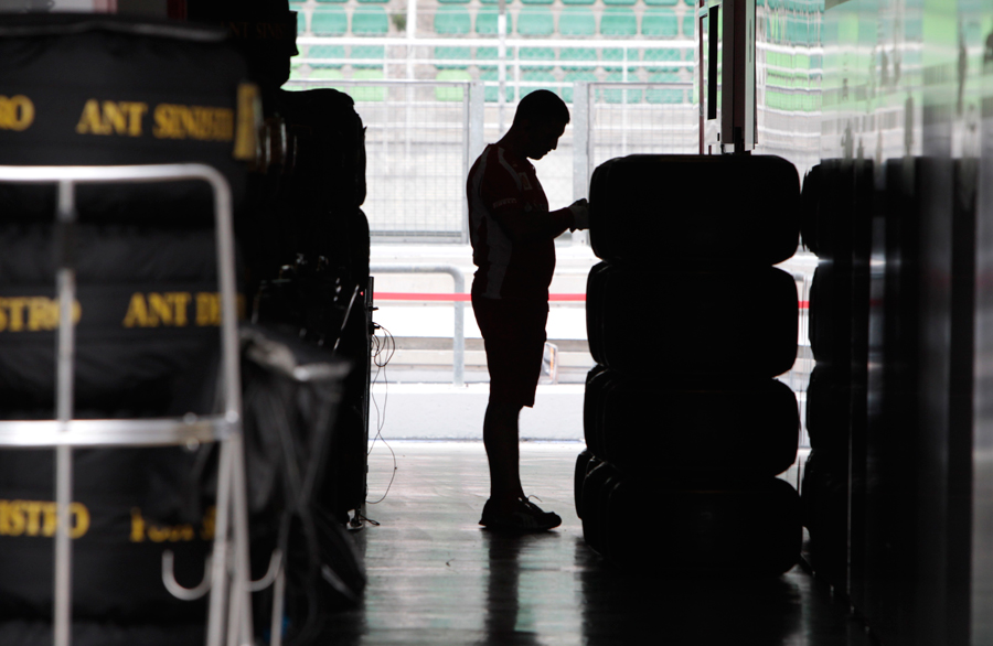A lone Ferrari mechanic checks tyres at Sepang