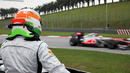 A sidelined Narain Karthikeyan watches Lewis Hamilton pass by