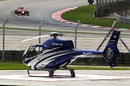 Timo Glock passes a parked helicopter during Friday practice