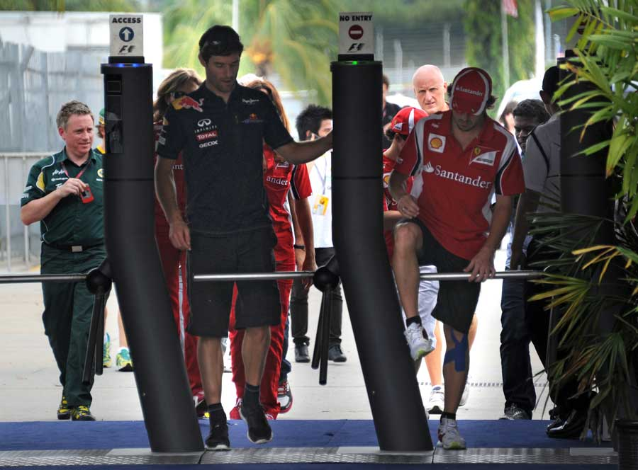 Fernando Alonso jumps the gates as he enters the paddock with Mark Webber