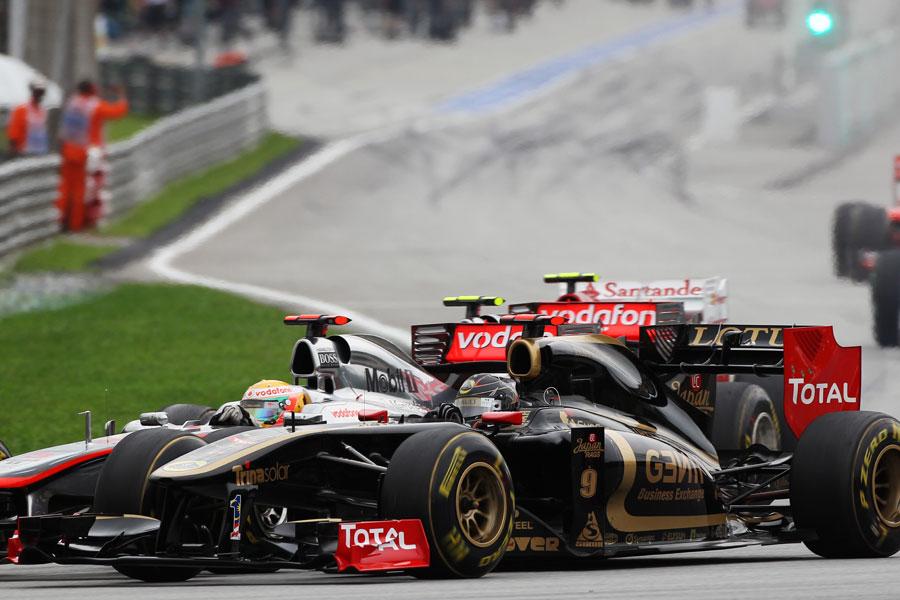 Nick Heidfeld takes Lewis Hamilton on the outside through turn one