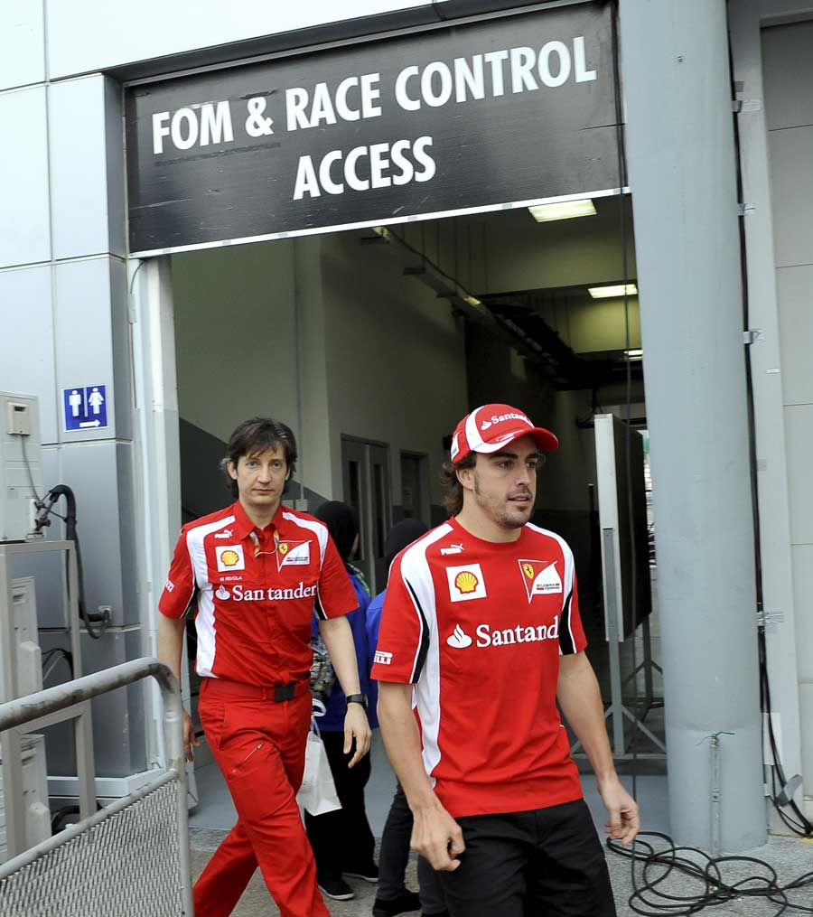 Fernando Alonso leaves the stewards' office after receiving a 20 second penalty for clashing with Lewis Hamilton