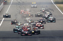 Jenson Button leads away as Lewis Hamilton pressures Sebastian Vettel