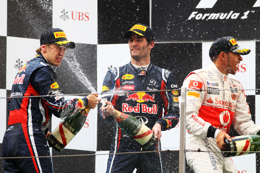 The Red Bull drivers and Lewis Hamilton spray champagne on the podium