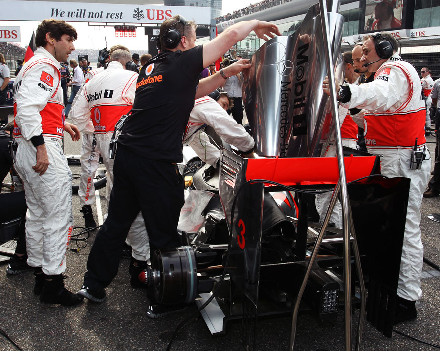 McLaren mechanics work on Lewis Hamilton's car on the grid